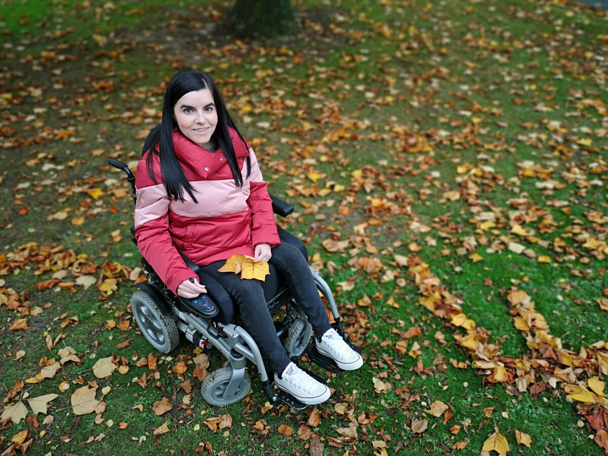 Emma is wearing a pink/red puffy jacket, black jeans and white converse shoes while sitting in her powered wheelchair. She is in her local park. Emma is looking up at the camera smiling.