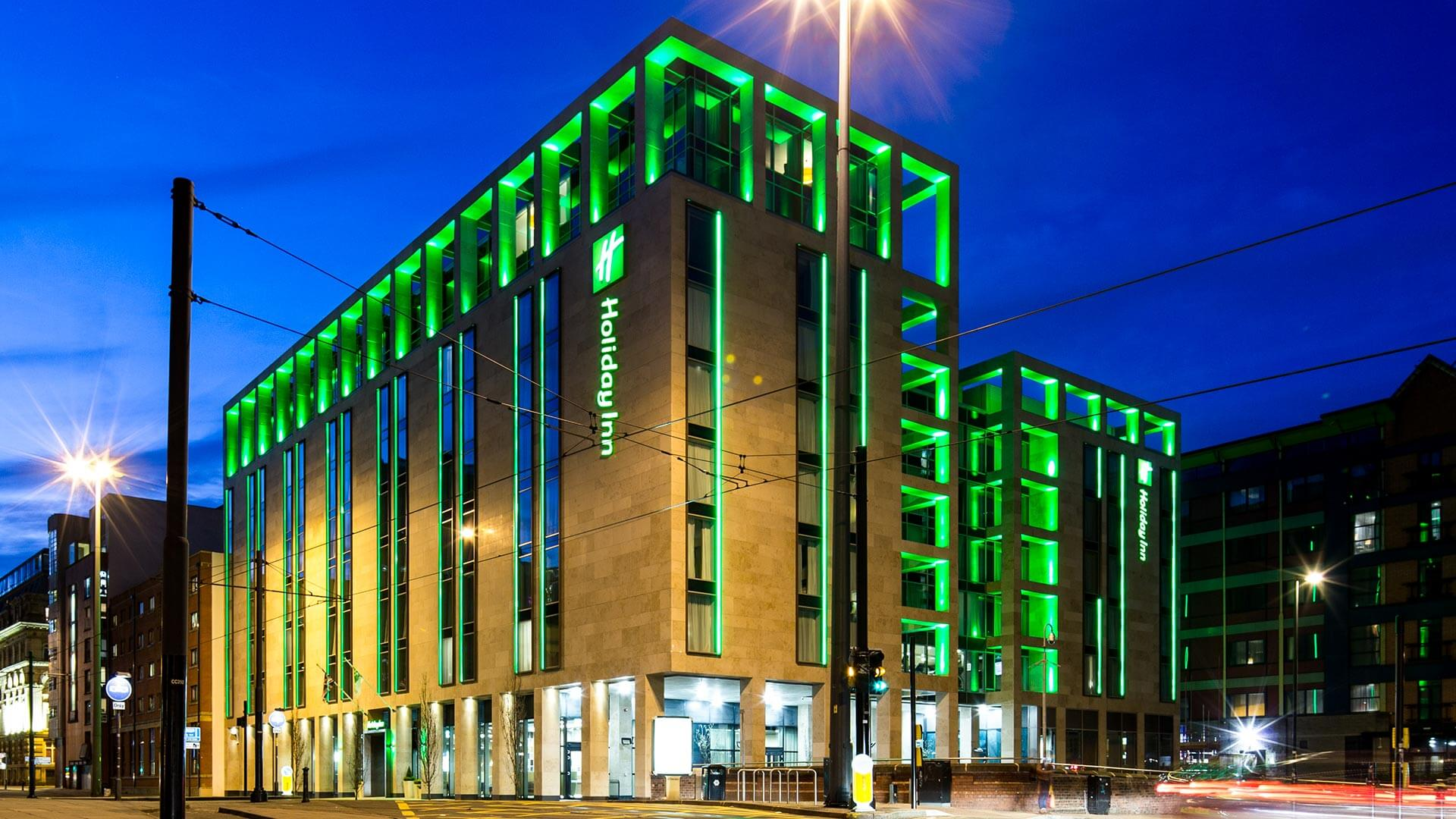A night time shot of the exterior of the hotel. It is lit up in green lights.