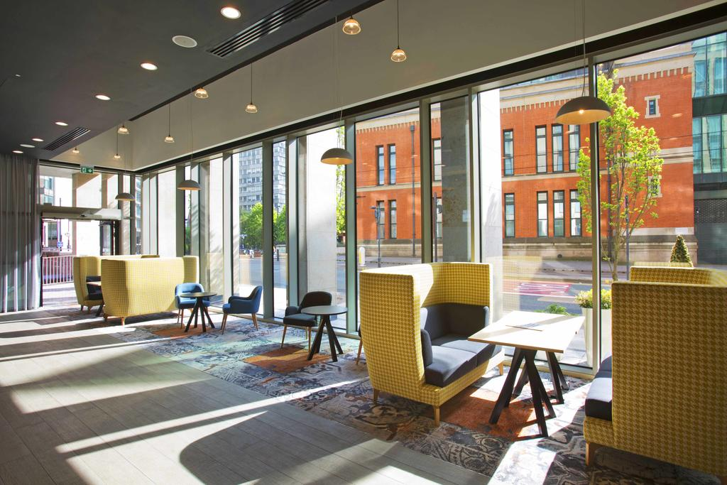 The reception and lobby area is open plan with large ceilling to floor windows bringing in lots of natural light. The furniture is light yellow and blue colours and in a very mid-modern style.
