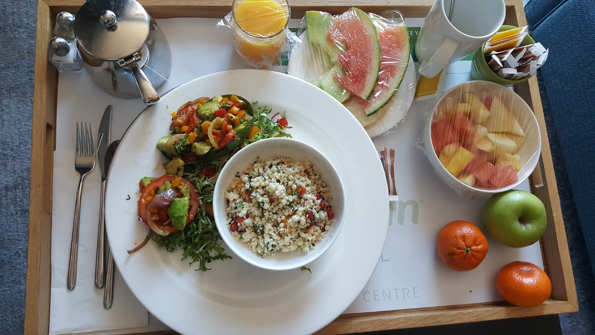 Room service tray filled with a delicious vegan breakfast consisting of couscous with chopped vegetables and pomegranates as well as a chopped avocado and vegetable salad on the side all with a delicious dressing. There was also a fruit platter including melon slices, apple and tangerines.