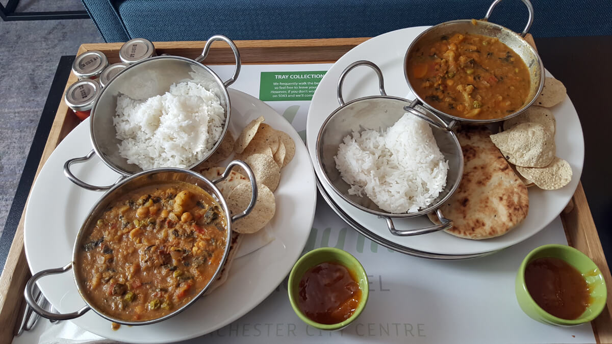 A room service tray with two vegan lentil dhal curries with boiled rice, naan bread and poppadoms.