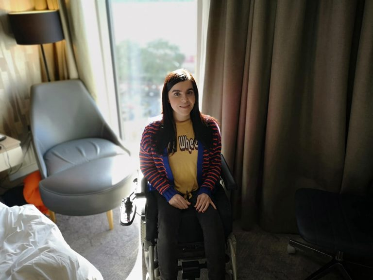 Emma is sitting in her hotel room wearing a yellow t-shirt with the words 'free wheelin' and a blue and orange stripey cardigan. She is looking at the camera smiling.