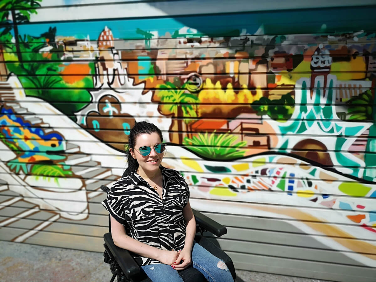 Emma sitting in front of a wall covered in amazing graffiti of Parc Guell, Barcelona. Emma is wearing a zebra print shirt, blue denim jeans, her hair is tied up and wearing sunglasses.