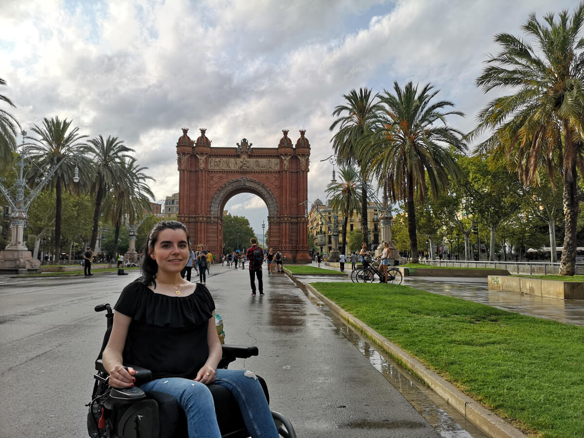 Emma is sitting in her wheelchair with the Arc de Triomf in the background. The sky is overcast after a thunderstorm.