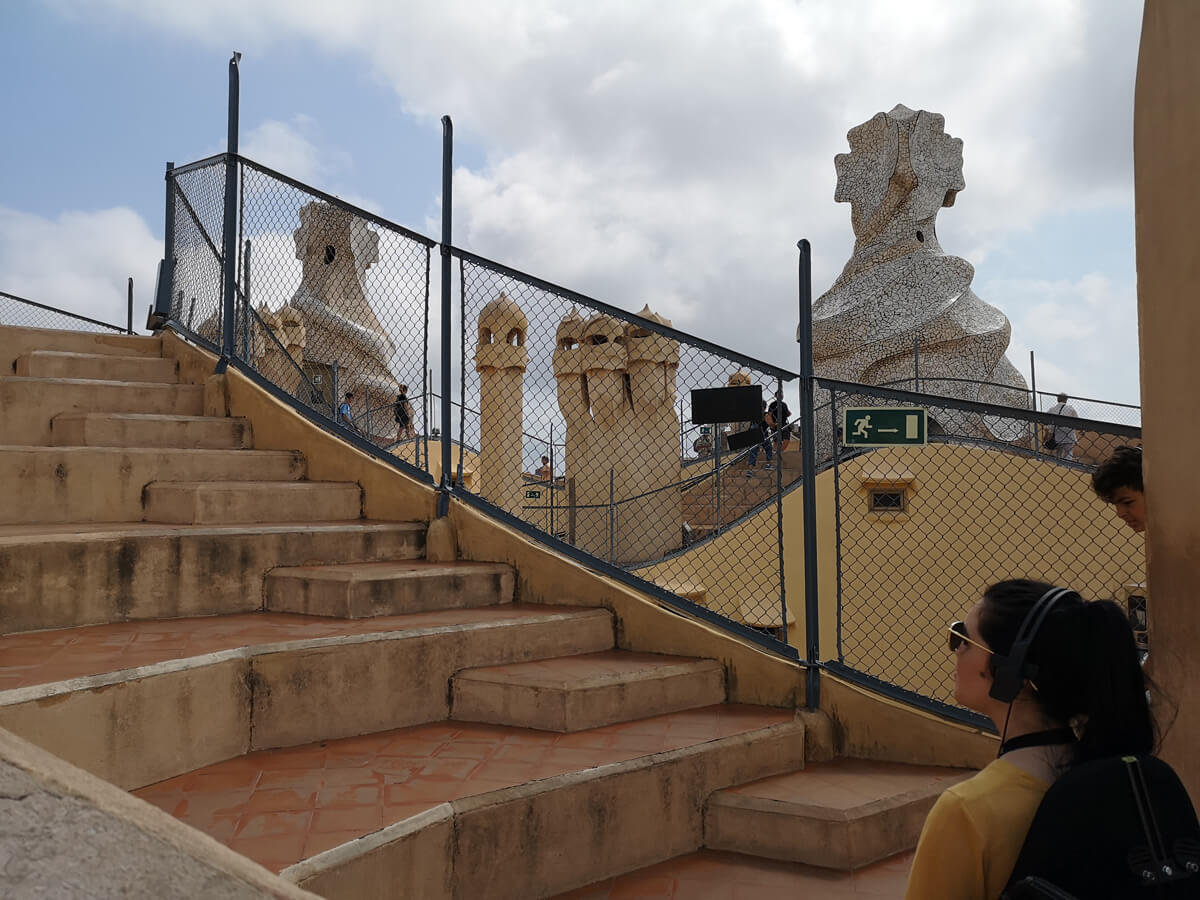 Emma is sitting on the roof of Casa Milà. She is unable to move around due to lack of wheelchair access. Emma is looking at the steps wearing the audio headset.