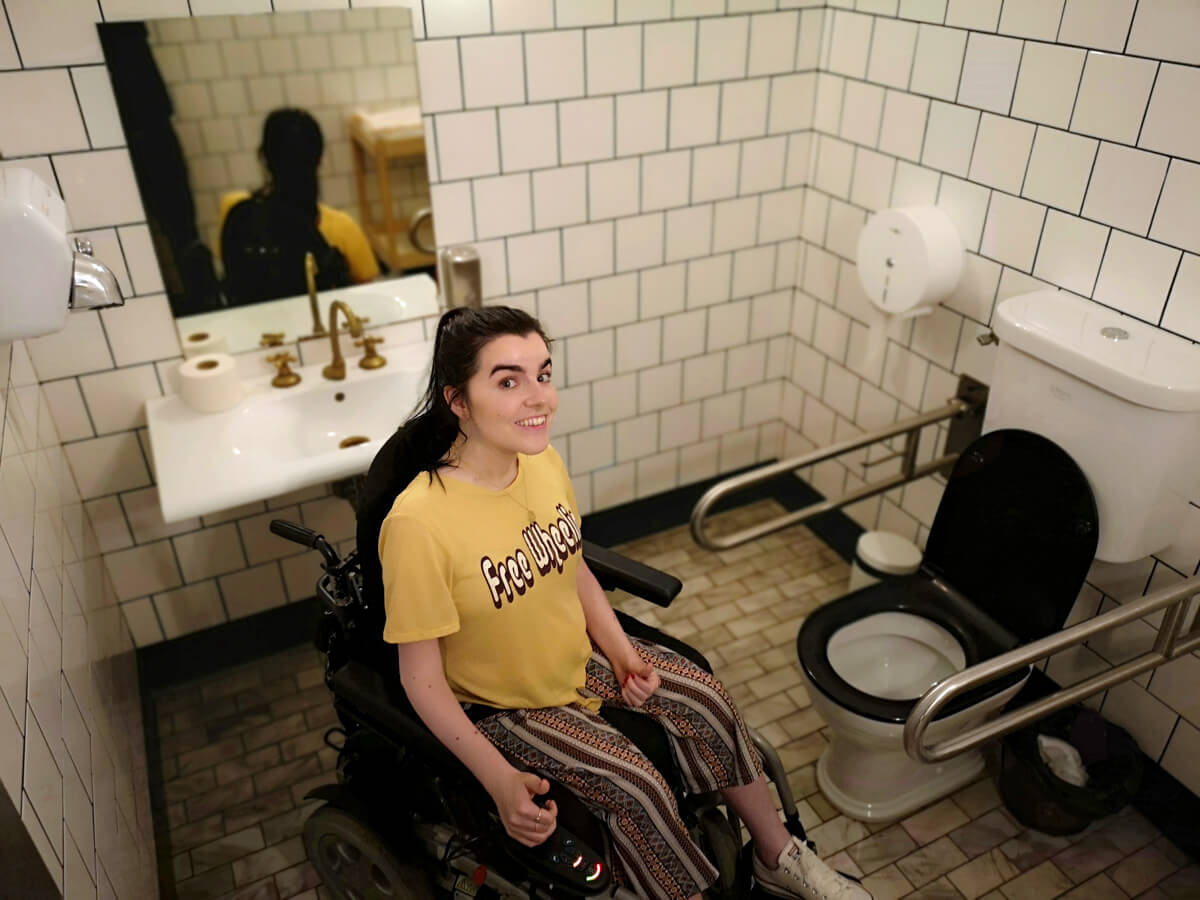 Emma is in the accessible toilet at Flax & Kale restaurant. She is smiling and wearing a yellow t-shirt with the words 'free wheelin'.