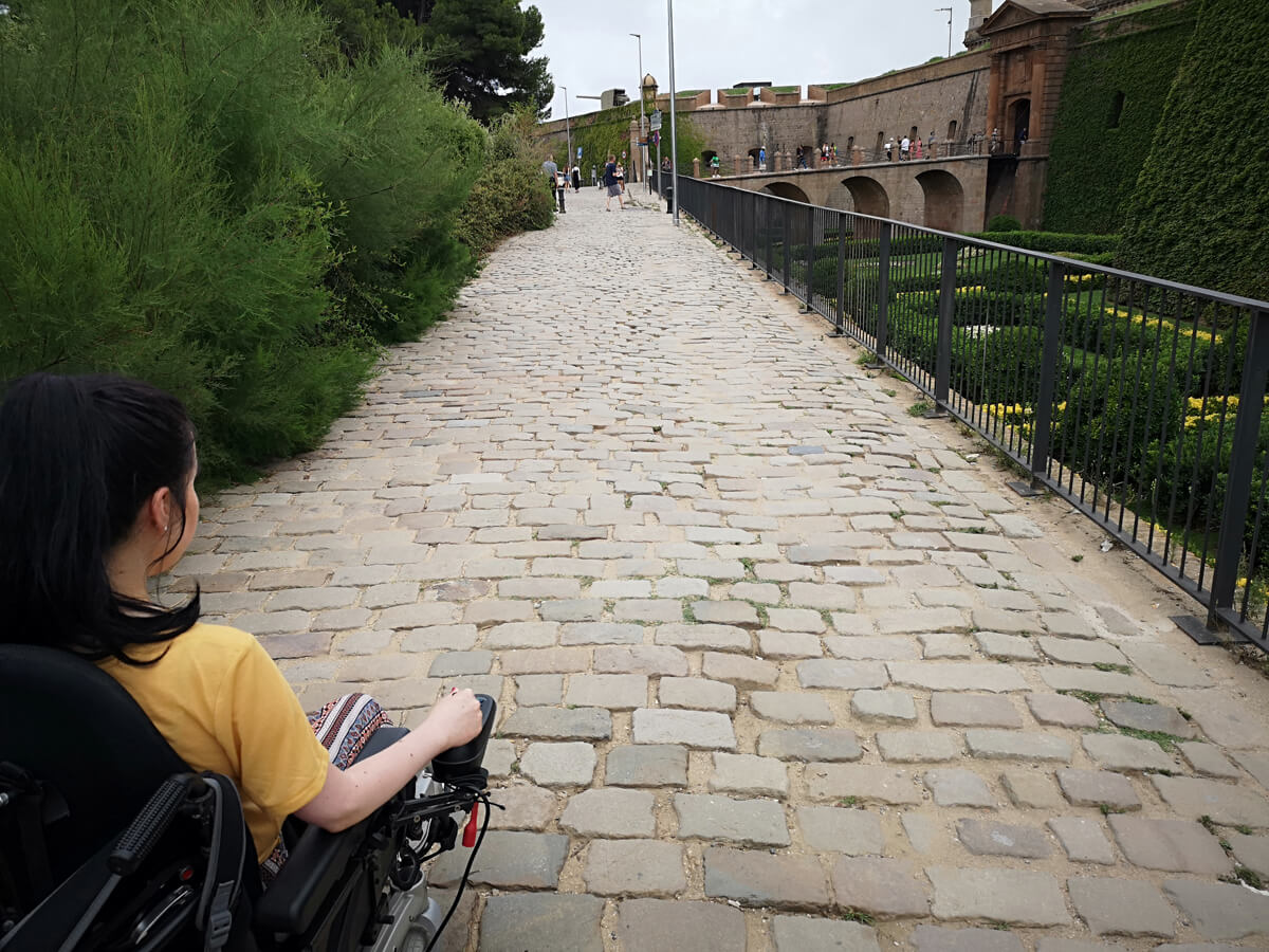 Emma driving her wheelchair along a cobblestone path towards Montjuïc Castle.