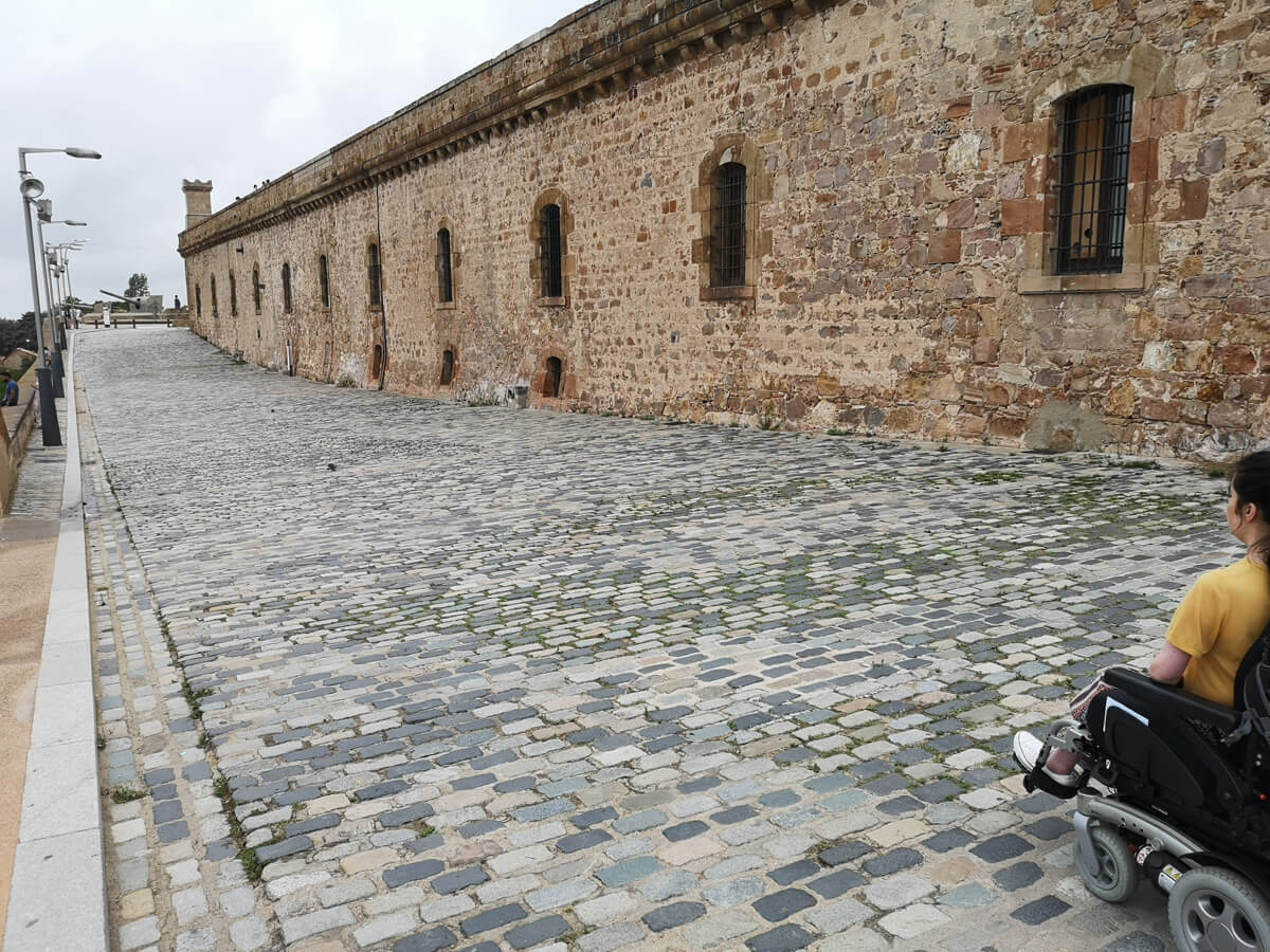 Emma driving her wheelchair along a cobblestone path around the grounds of Montjuïc Castle.