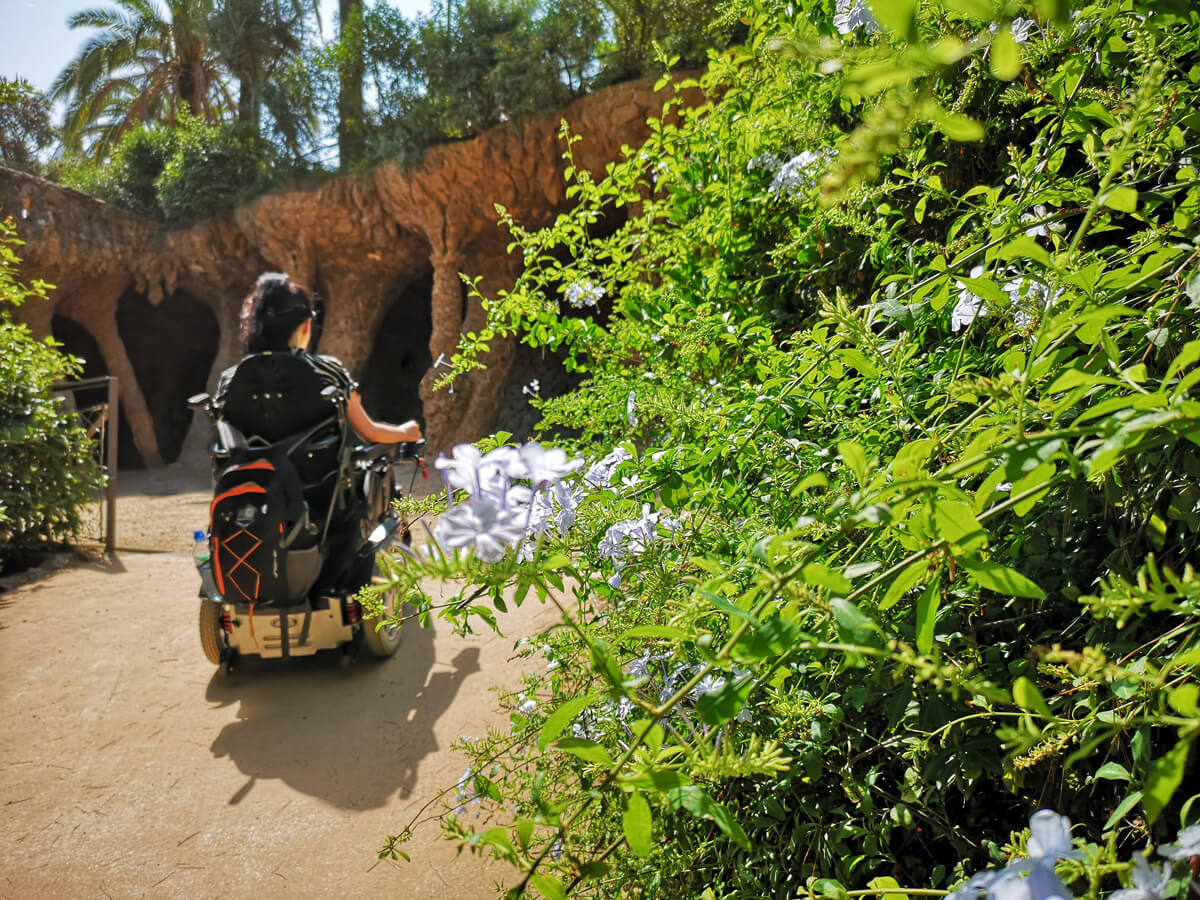 Emma is driving her wheelchair up a slight slope in Parc Guell.