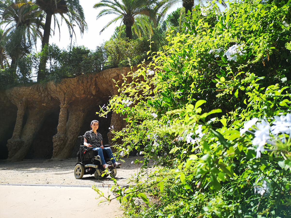 Emma is in her powered wheelchair sitting in front of a stone cave.