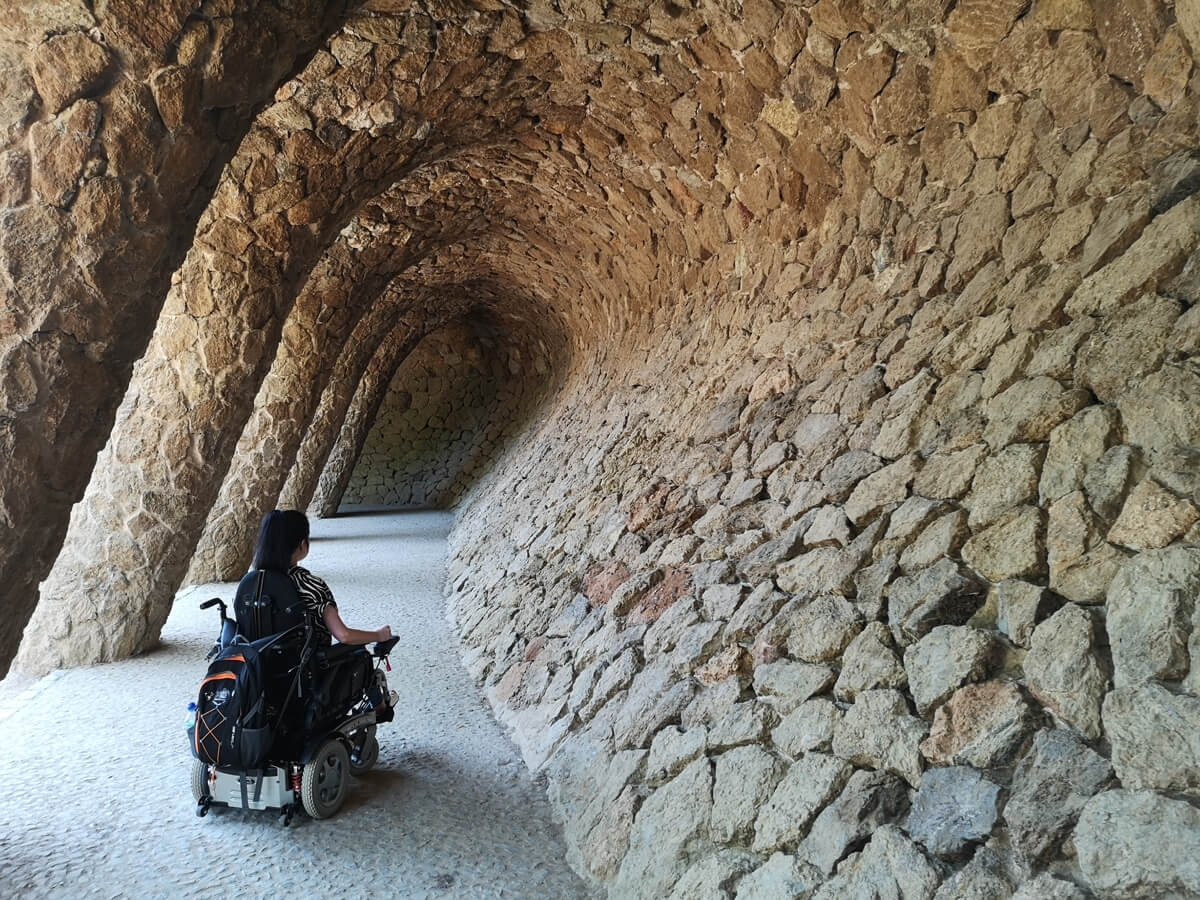 Emma is in her powered wheelchair facing away from the camera. She is under a stone archway in Parc Guell.