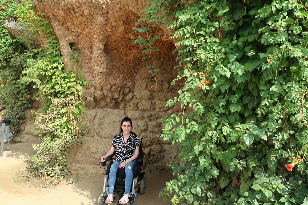 Emma is sheltering from the sun under a stoney arch in Parc Guell. Emma is wearing skinny jeans and a zebra print shirt.