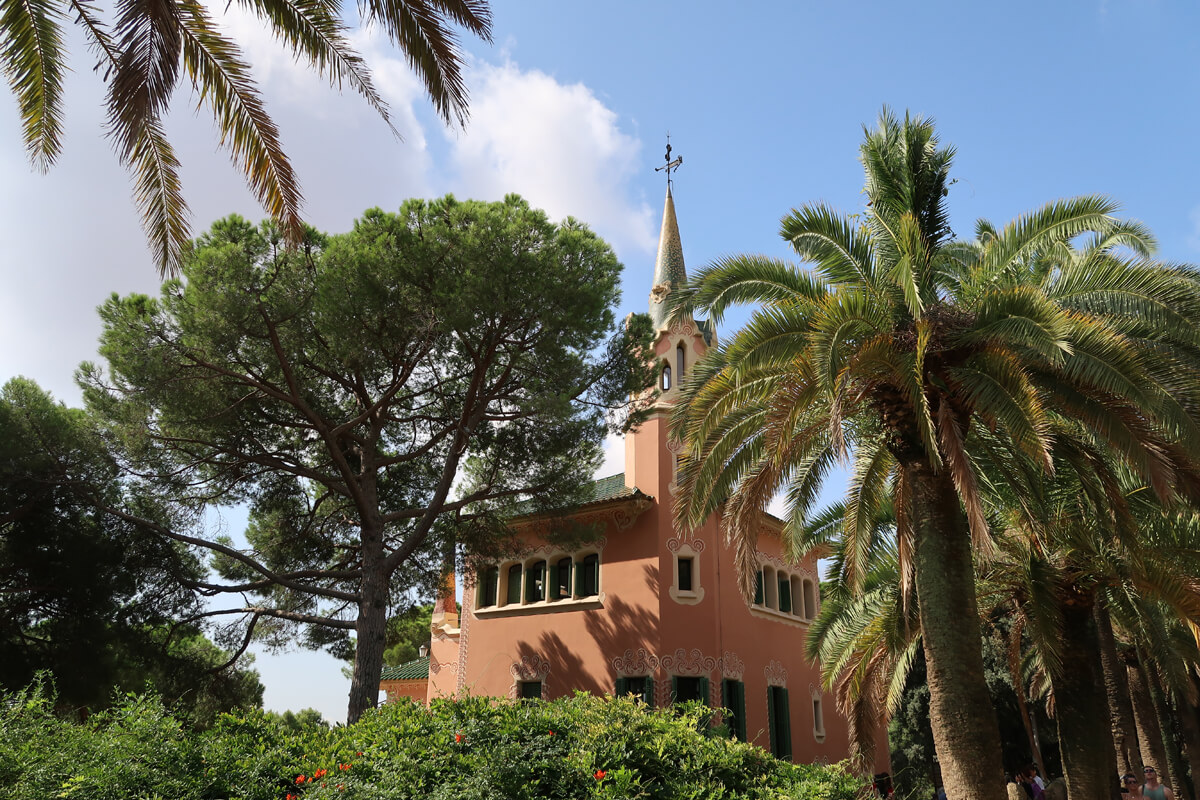 A salmon colored house surrounded by green palm trees.