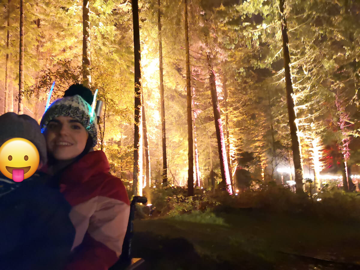 Emma and her nephew with lovely lit up trees behind them. Her nephews face is covered by a smiley sticking tongue out emoji.