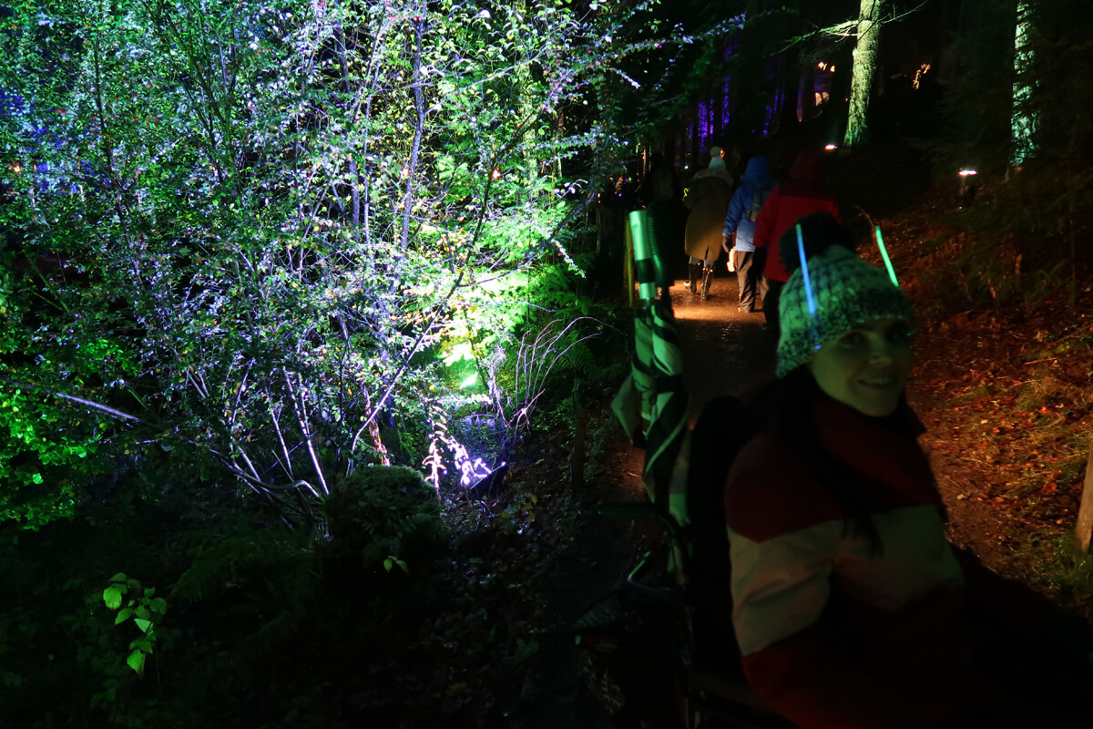 Emma smiling with two glow sticks in her woolly hat.