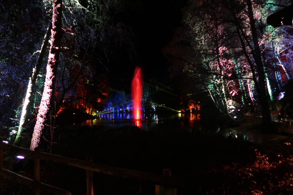 A water fountain in the middle of the water. The water is lit up red.