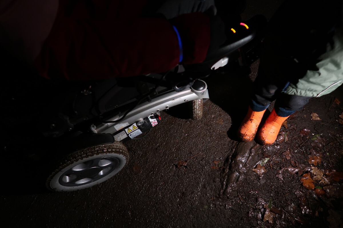 An image of the wheels of Emma's wheelchair covered in mud alongside her nephews muddy orange wellington boots.