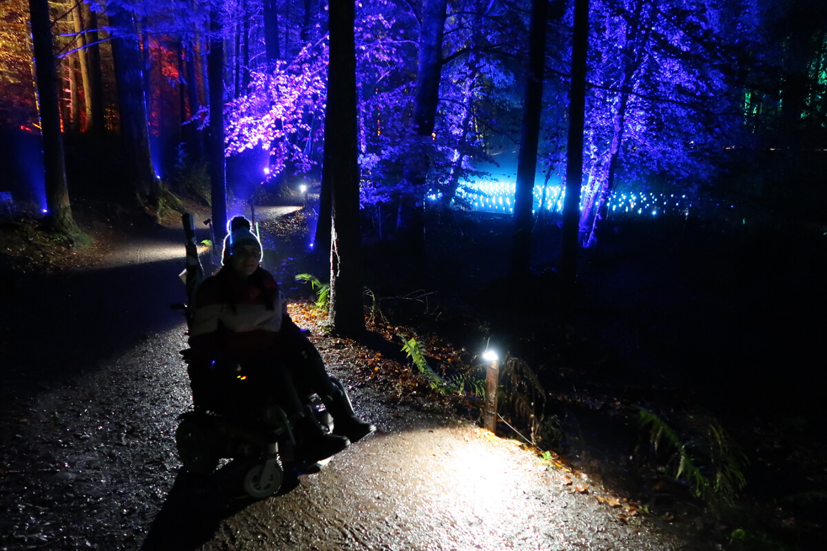 Emma sitting in her powered wheelchair on a muddy path with purple lit up trees behind her.