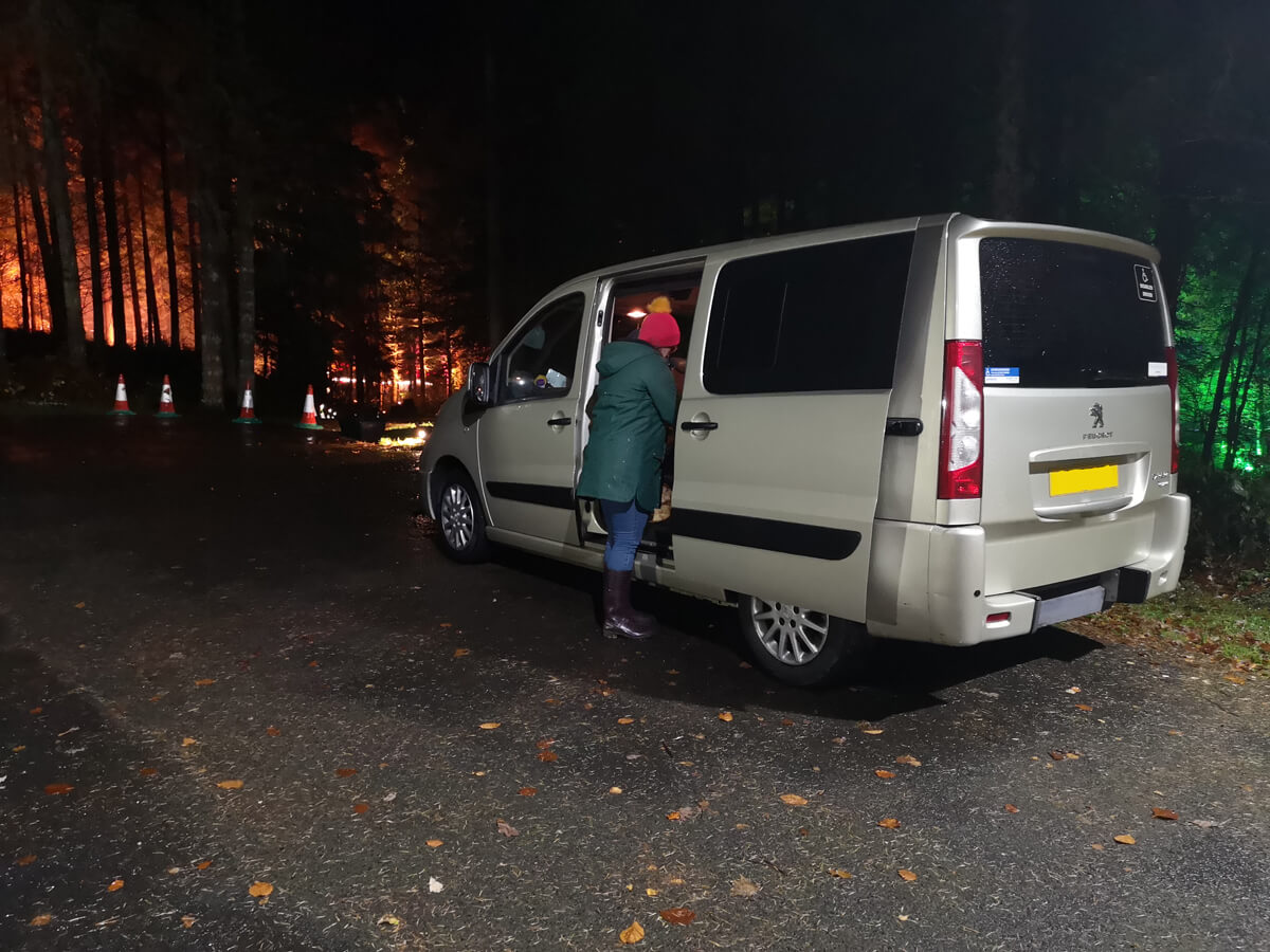 My sister standing at the passenger door of our van in the disabled parking area.