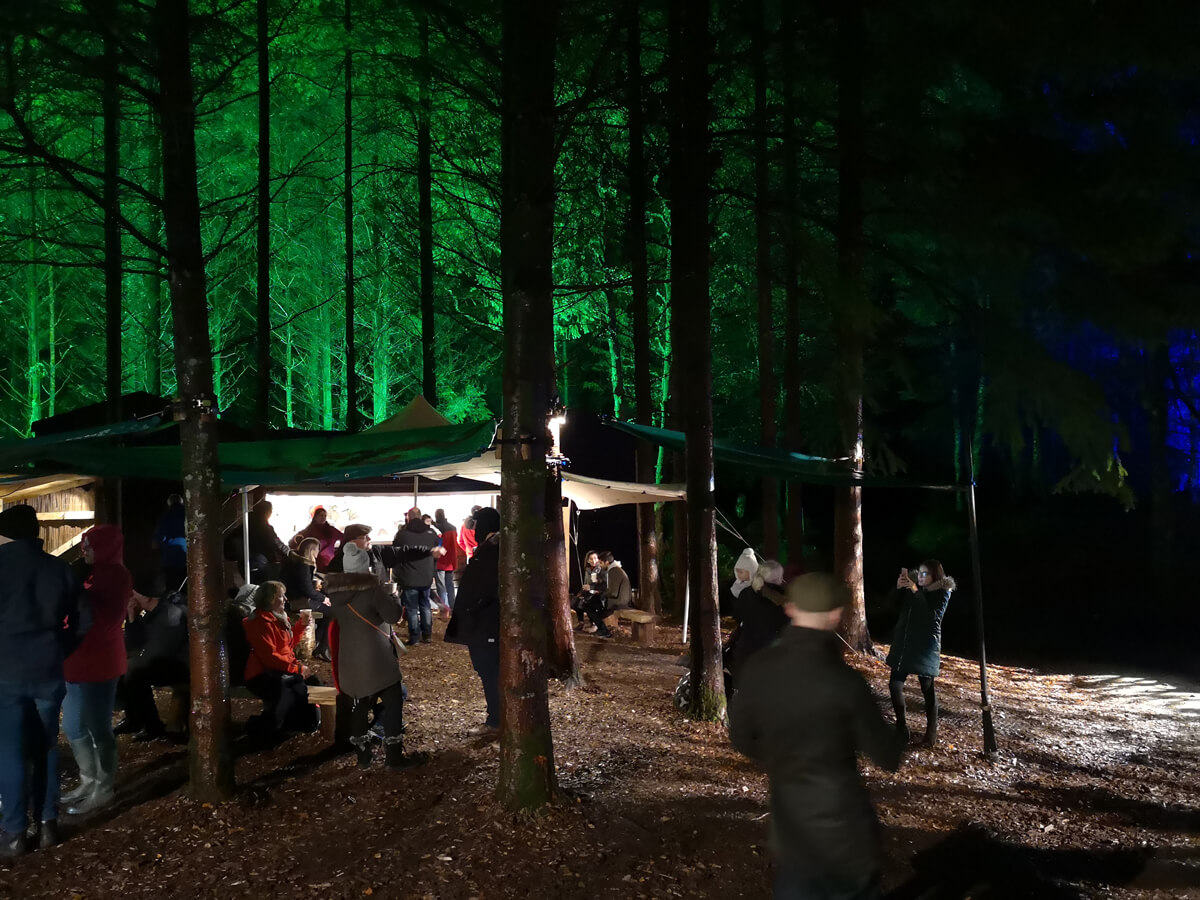A food and drink tent surrounded by green lit up trees.