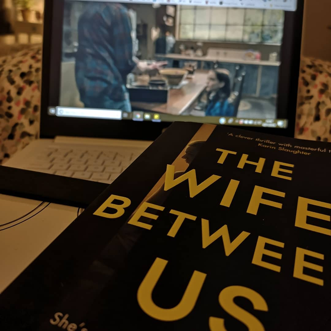 A book called 'The wife between us' laying across a laptop which has A Haunting of Hill House playing on the screen.