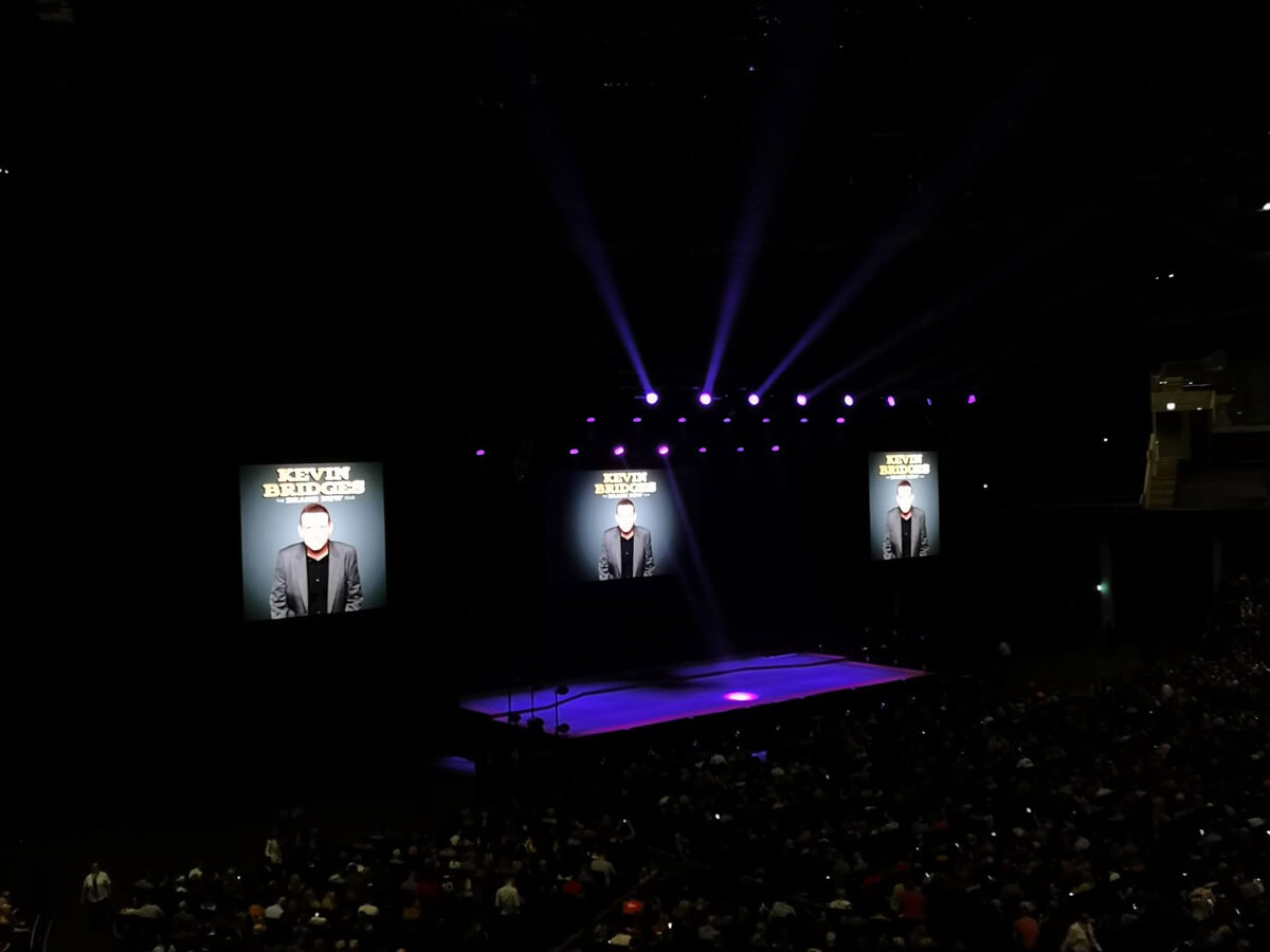Inside the SSE Hydro Arena. A view of the stage from level 2 accessible seating. The stage is lit up with three large screens with Kevin Bridges photo and name.