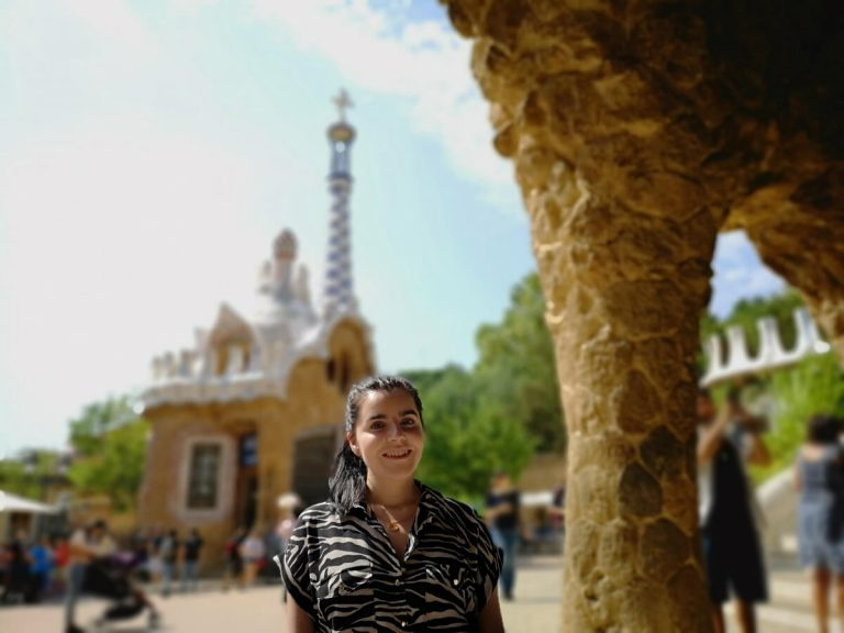 Emma is wearing a zebra print shirt. She is facing the camera with a ginerbread house behind her in Parc Guell.