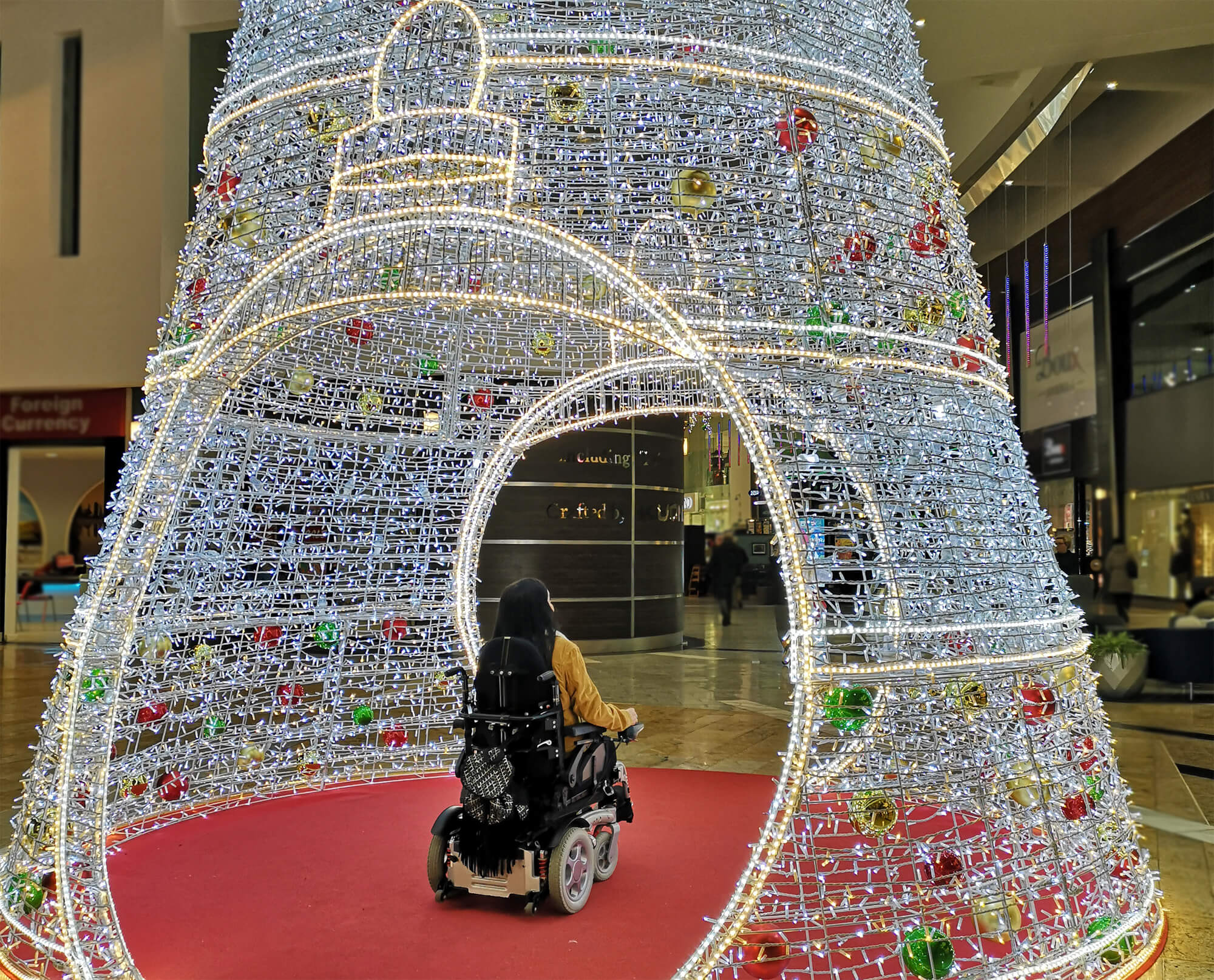 Emma in her powered wheelchair sitting inside a decorative Christmas tree and Christmas light display in Silverburn Shopping Centre.