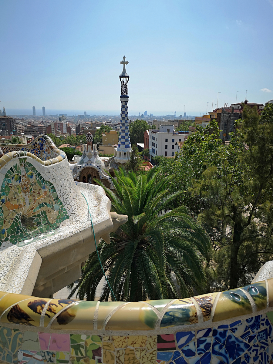 The view of Barcelona from the top of Parc Guell. The colorful mosaic wall frames the bottom of the photo.