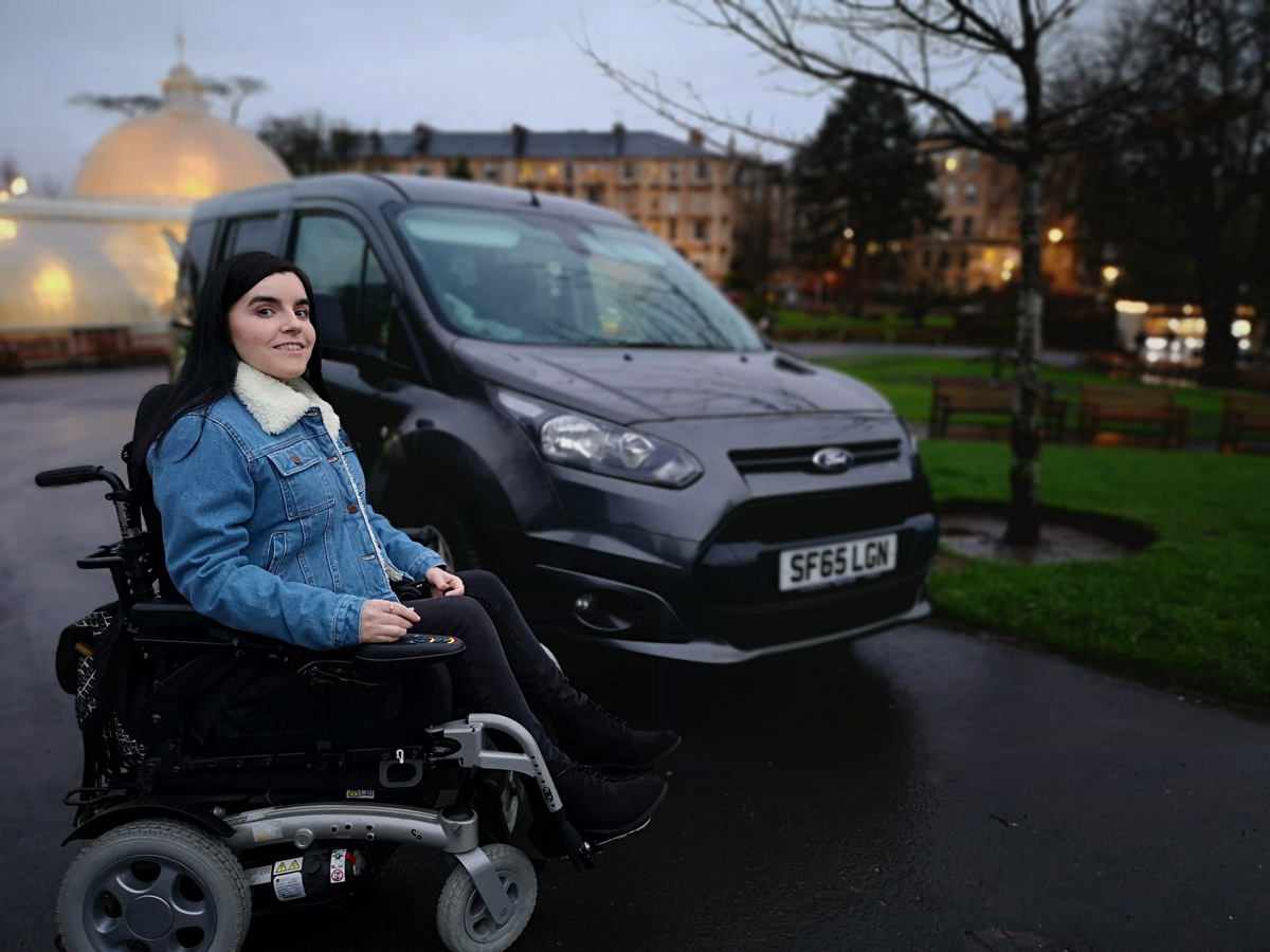 Emma sitting infront of her Ford wheelchair accessible car at Glasgow Botanic Gardens.