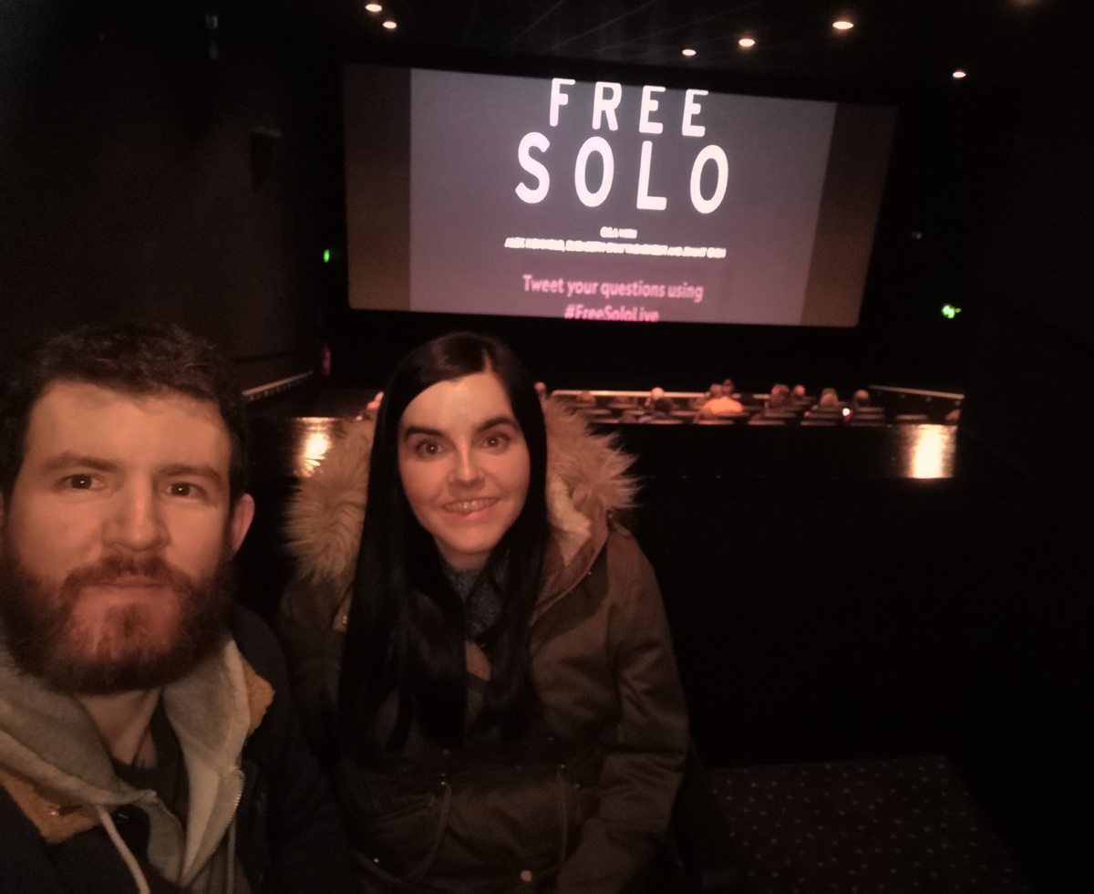 Emma and Allan sitting in a private wheelchair accessible booth at the cinema. Behind them is the movie screen with the words 'Free Solo'.