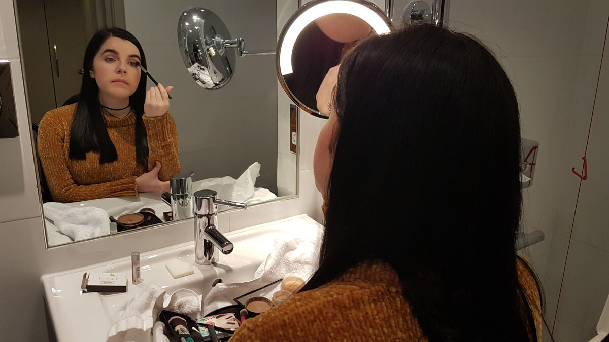 Emma sitting at the bathroom sink in her hotel room applying her makeup. She is looking into the mirror and her makeup is placed on the bathroom sink.