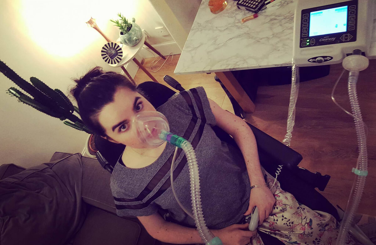 Emma wearing a mask over her mouth and nose which is attached to a Cough Assist machine to help her cough.