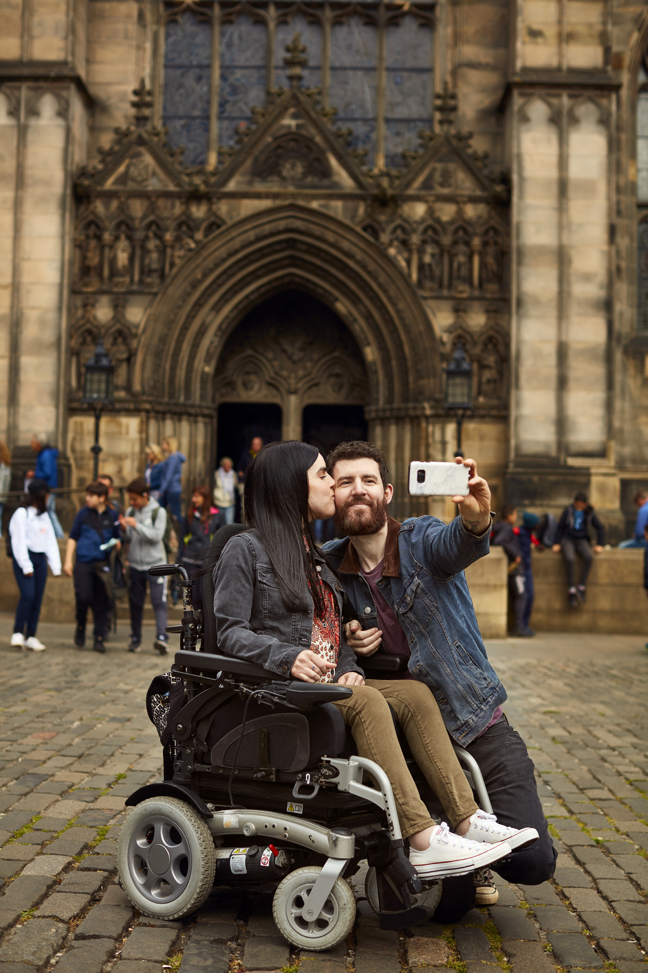 Emma and Allan posing for a selfie outside St Giles' Cathedral in Edinburgh. Emma is giving Allan a peck on the cheek.