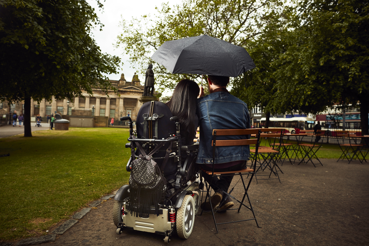 Emma and Allan sitting at a kiosk in Princes Garden, Edinburgh. They are sitting at a table with their backs to the camera. Allan is holding an umbrella over them.