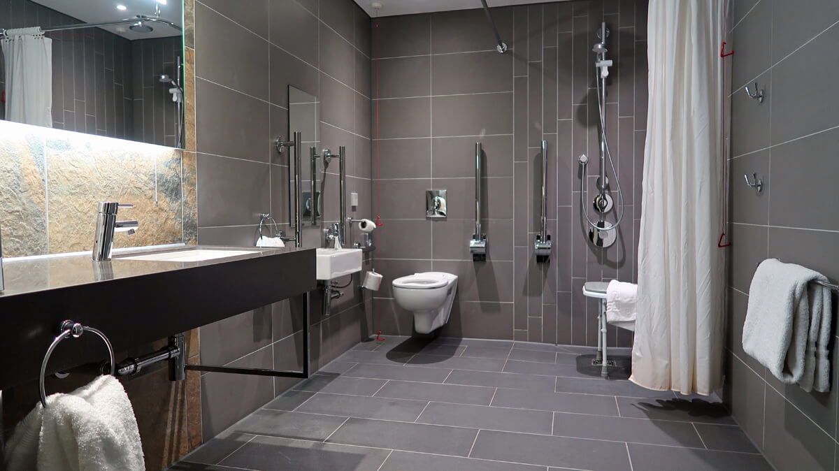 Accessible bathroom in DoubleTree Sheffield Park. Roll in shower, toilet with grab bars and roll-under sink. Stylish design with grey slate wall and floor tiles.