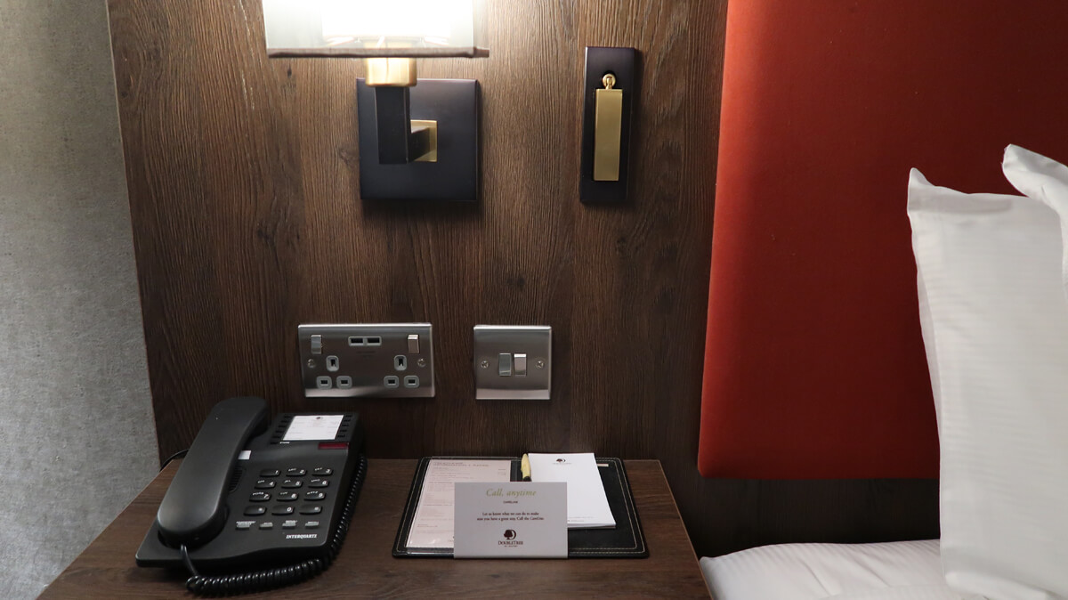 Bedside table with telephone, power sockets, notepad, pen and lamp.