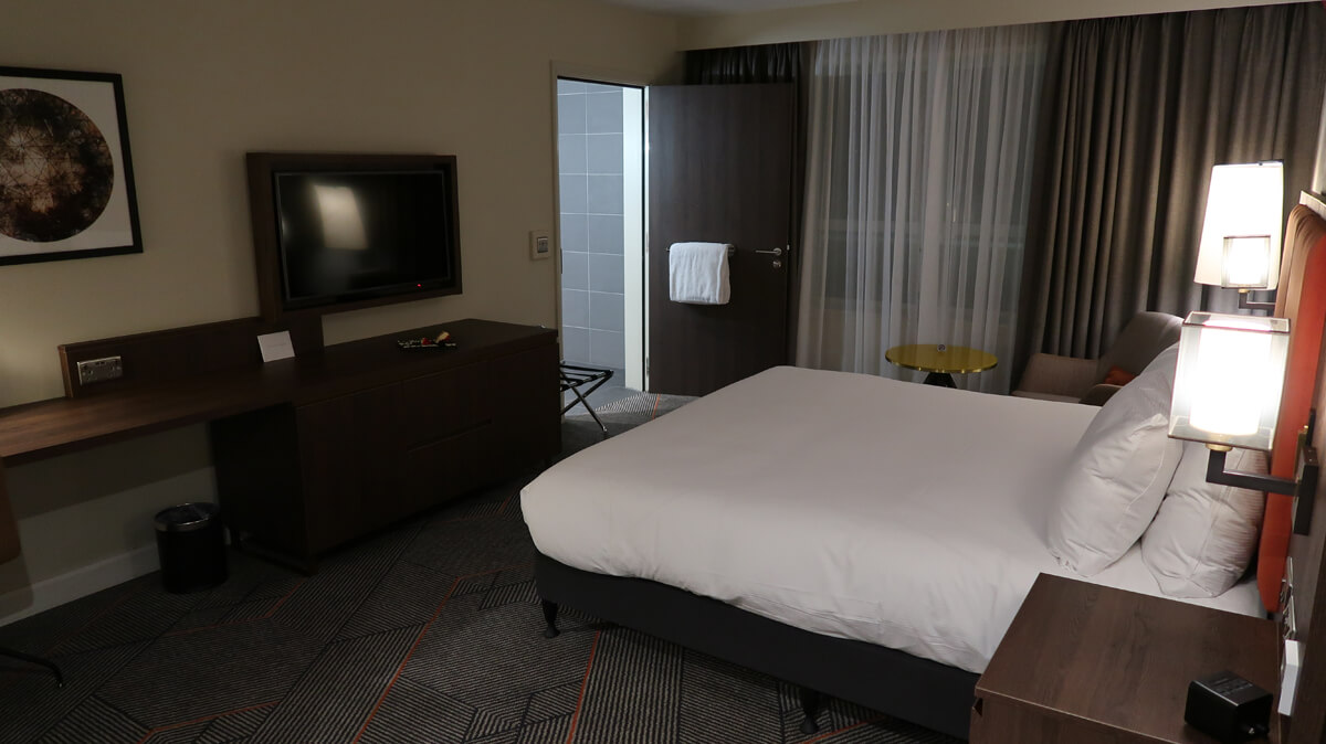 A view of the room showing the bed, desk and bathroom door.