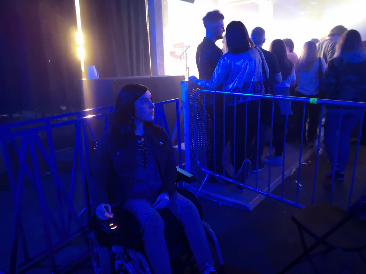 Emma sitting inside the barrier of the viewing area for wheelchair users.