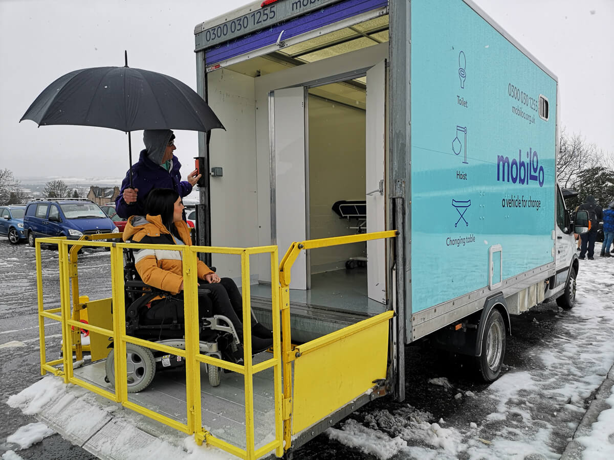 Emma, a power wheelchair user entering the Mobiloo with the driver/attendant Rich standing next to her while holding an umbrella over her to shelter from the snow.