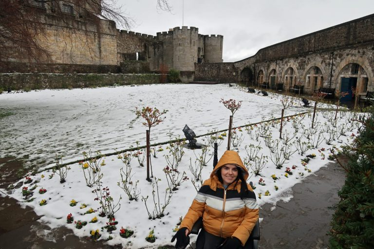 Emma sitting in her wheelchair in the snow covered gardens.