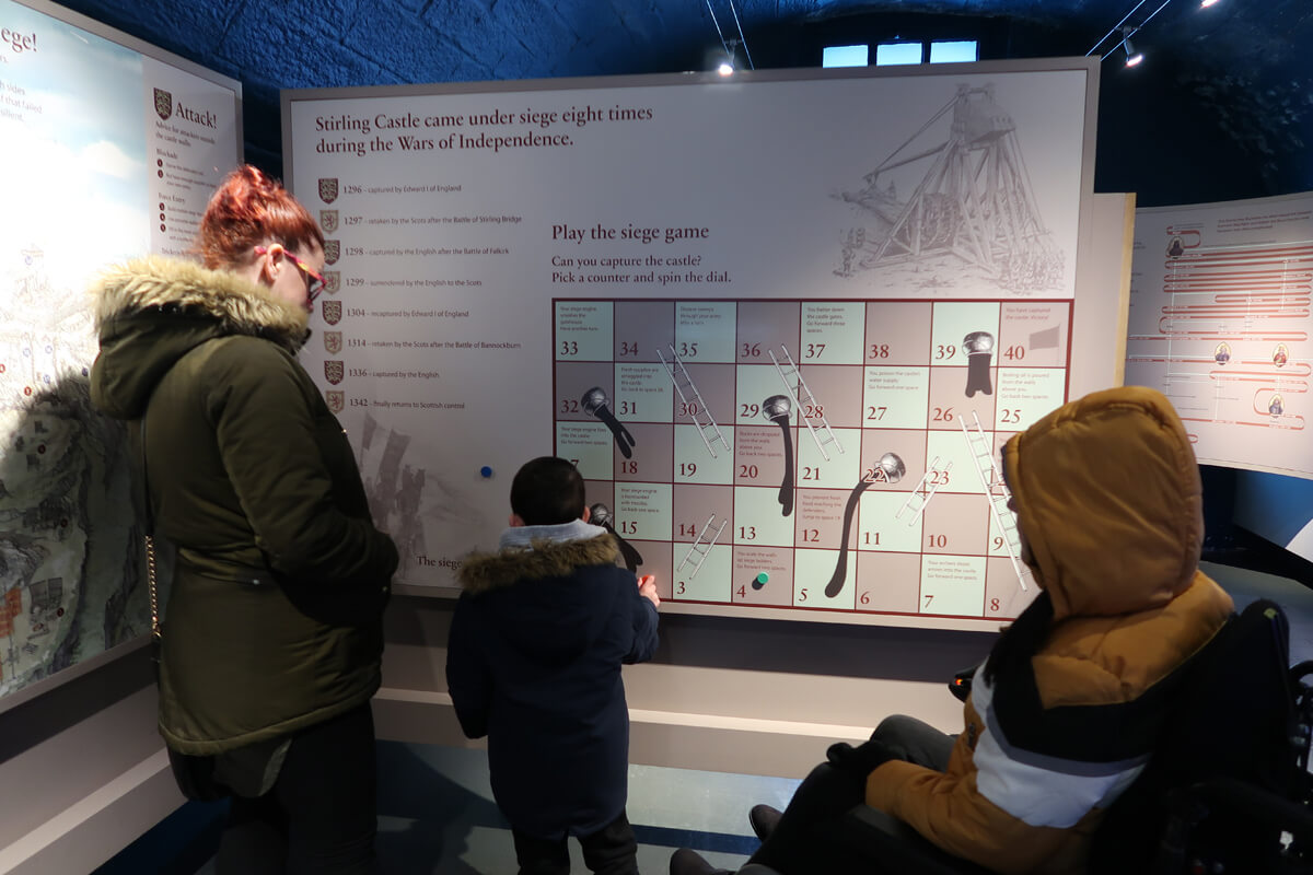 Emma, her sister and nephew playing an interactive game in the access gallery at Stirling Castle.