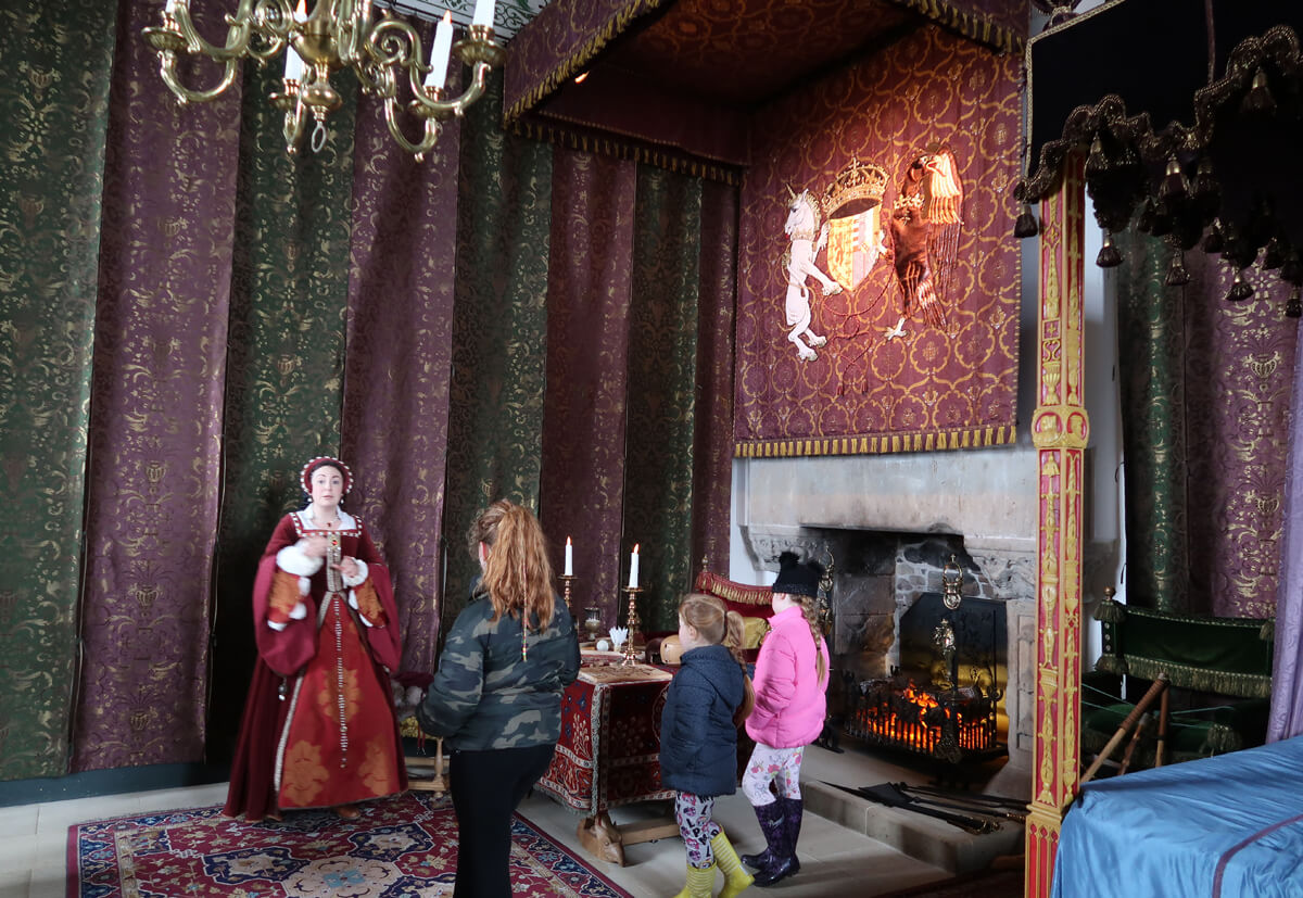 A woman dressed up in costume inside the Queen's bedroom.