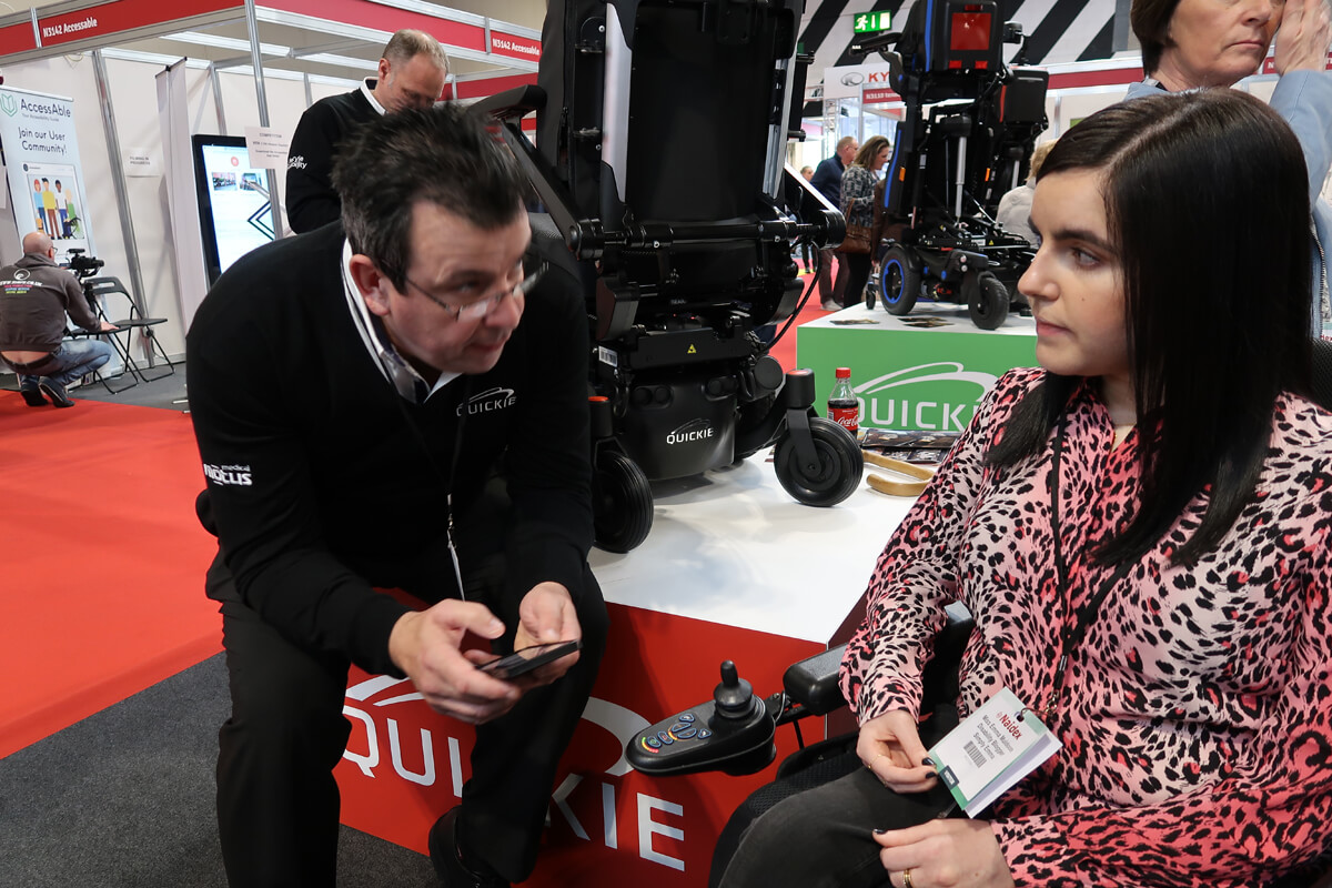 Emma speaking to a Quickie wheelchair sales rep at Naidex 45.