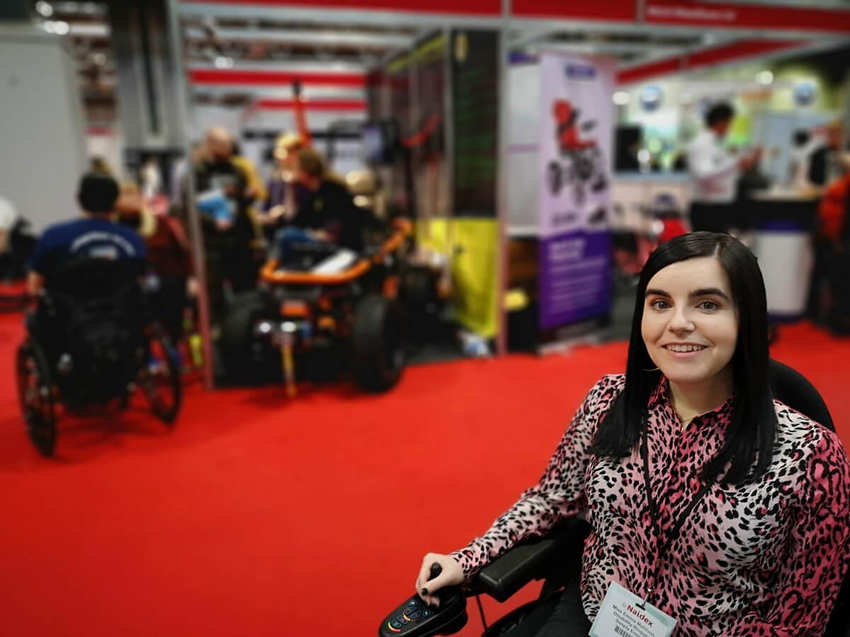 Emma sitting beside an all-terrain wheelchair.