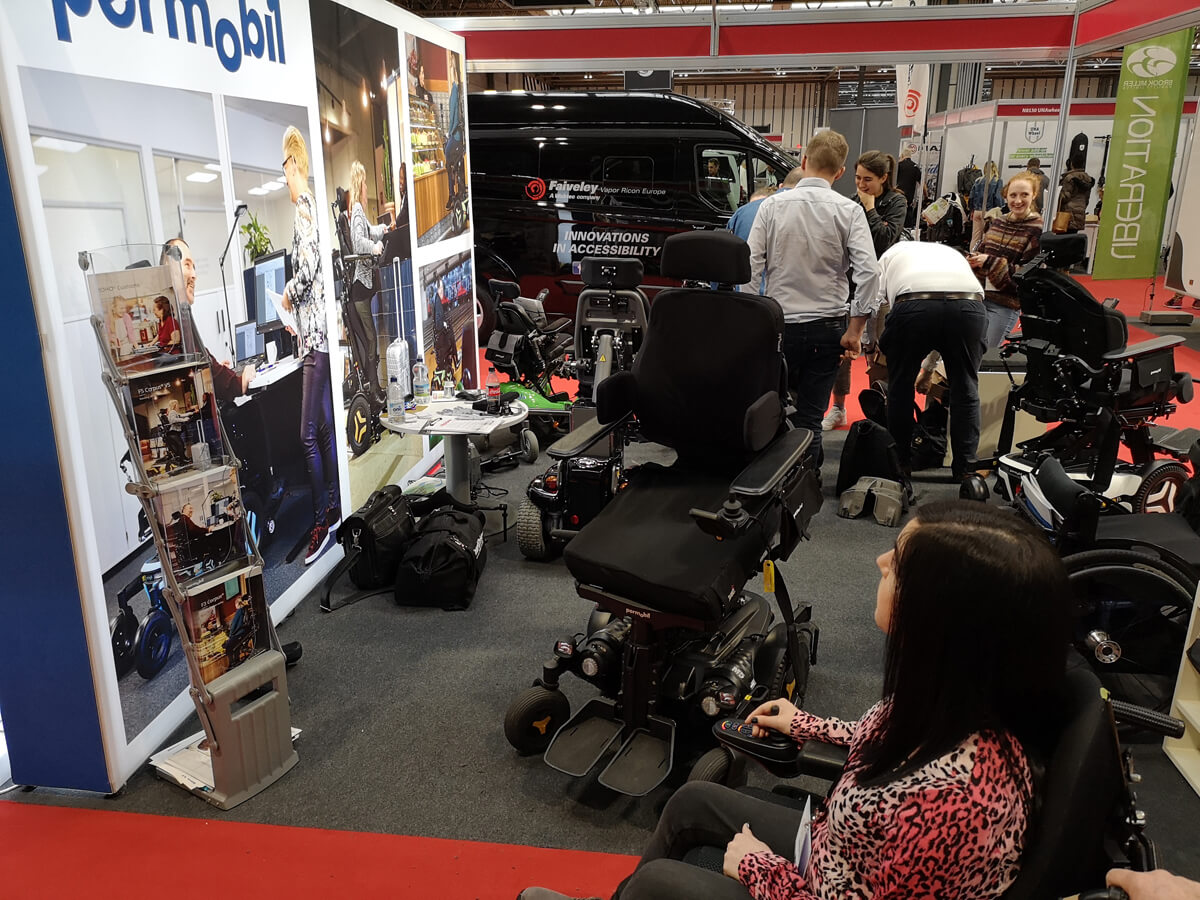 Emma looking at the Permobil wheelchairs on display at Naidex 45.