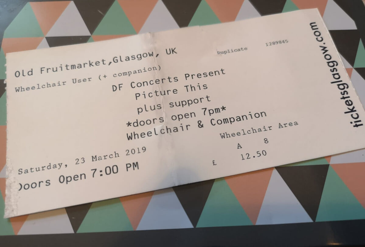 Picture This gig ticket laying on a coloured geometric surface.