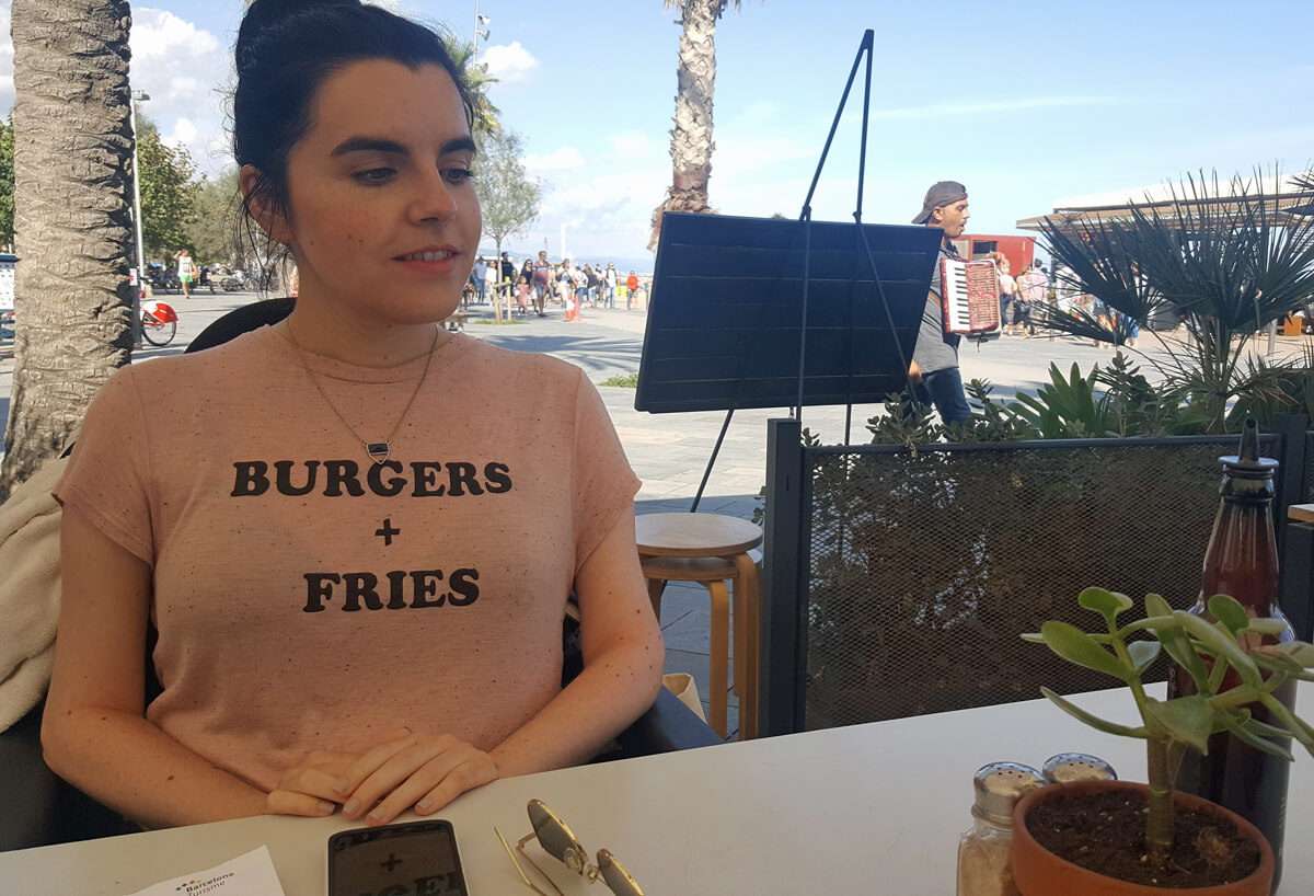 "Emma sitting at Bacoa Barceloneta on the beach front. Emma is wearing a t-shirt with the words ""Burgers + Fries""."