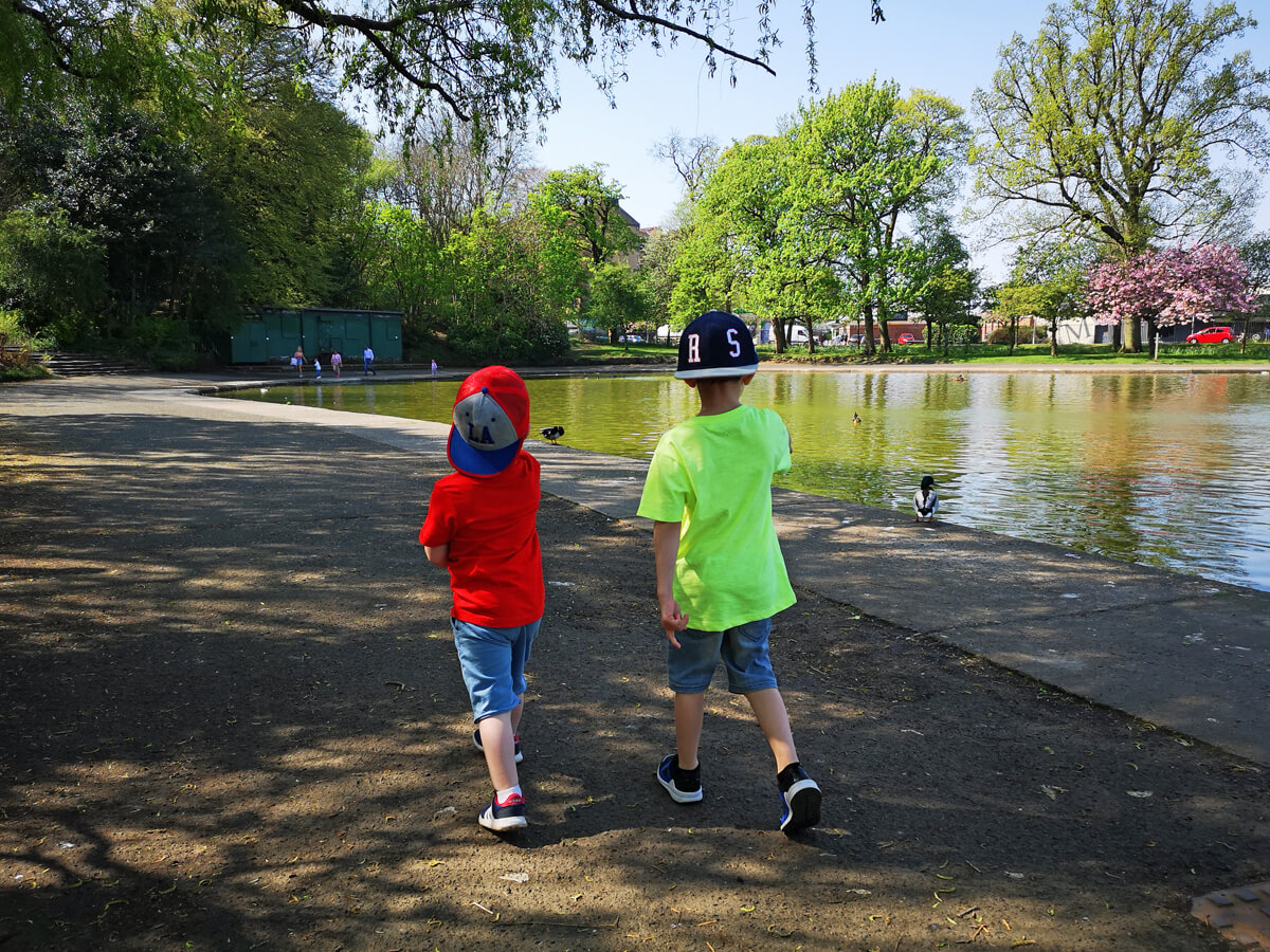 Emma's two nephews walking alongside pond in the park during a sunny day.