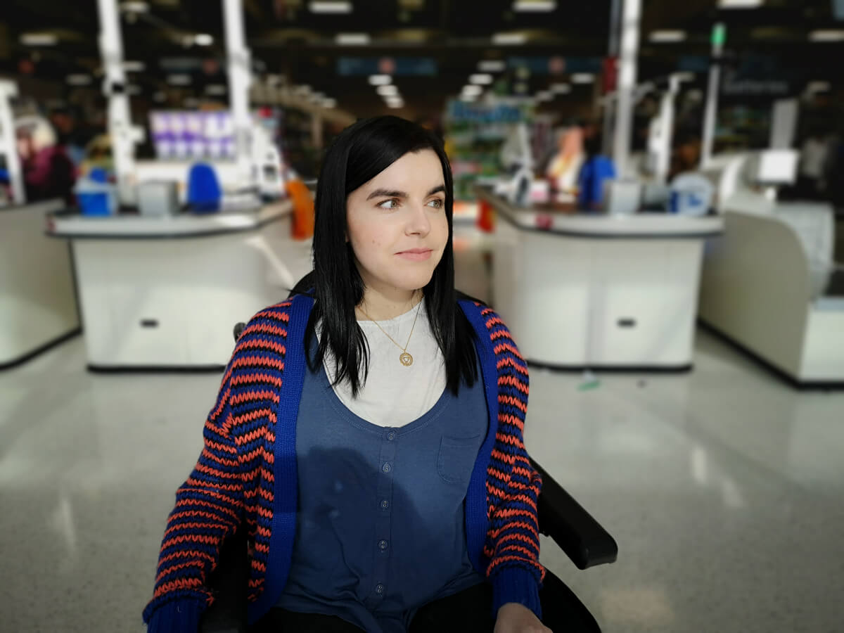 Emma is in a supermarket. She is wearing a blue and orange stripey cardigan with a blue and white top.